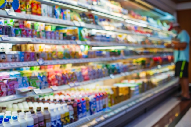 散瞳異常男性の買い物用ミルクを健康のためにスーパーマーケットの食品に置いた買い物棚。