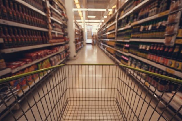 スーパーマーケットの床のドライフードに置かれた男性と女性のカート購入ショッピングの焦点がぼけたぼやけ