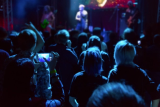 Defocused blurred image of people crowd at concert and stage neon lights.