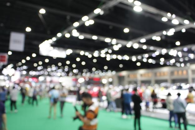 コンベンションイベントや会議場の展示会見本市を歩いている、焦点がぼけたぼやけた群衆の匿名の人々。明るいボケ味の背景。