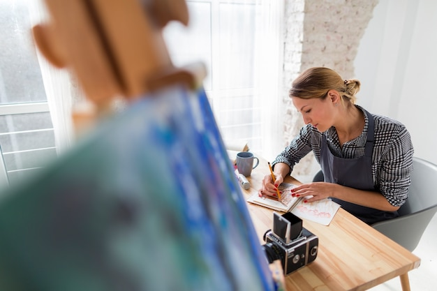 Defocused canvas with artist in apron at desk