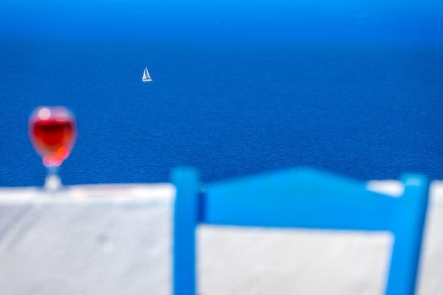 초점이 흐려진 의자와 와인 한 잔, 그리고 멀리 바다로 항해하는 흰색 요트