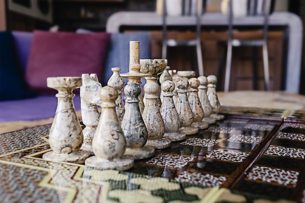 Defocused chess board with marble brown and black figures
