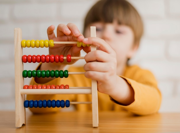 Defocused child learning how to count using abacus