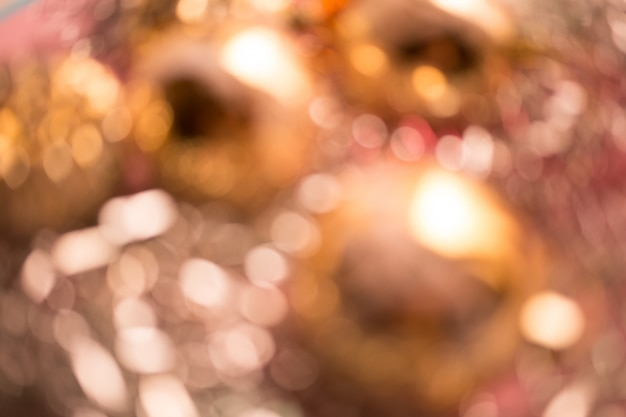 Defocused christmas composition. christmas golden and pink balls. blurred abstract background.