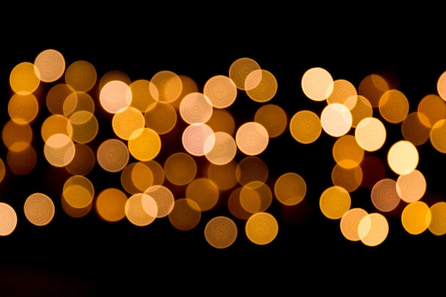 Defocused city gold night bokeh abstract background. blurred many round yellow light on dark background.