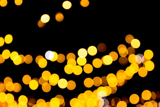Defocused city gold night bokeh abstract background. blurred many round yellow light on dark background