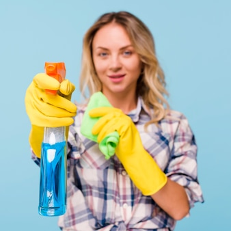 Defocused cleaner woman spraying detergent bottle with holding napkin in her hand against blue background