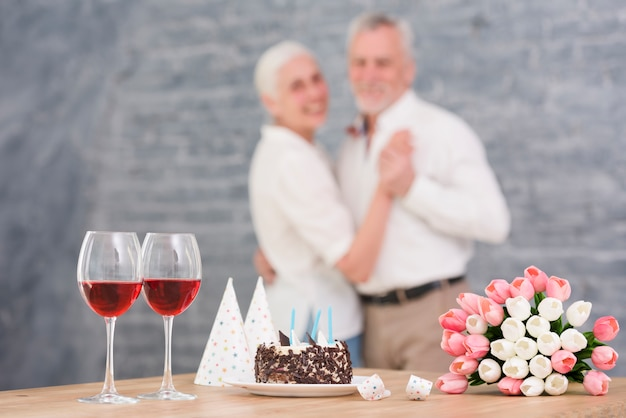 Defocused couple dancing in front of wine glass; delicious cake; tulip flowers on wooden table