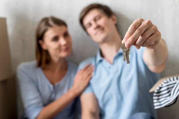 Defocused couple holding keys to old house before moving out
