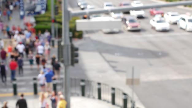 Defocused crowd of people, road intersection crosswalk in las vegas, usa. pedestrians on walkway.
