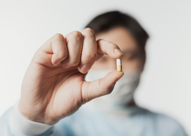 Defocused doctor holding up pill in hand