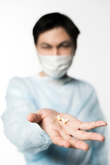 Defocused doctor with medical mask holding pills in hand