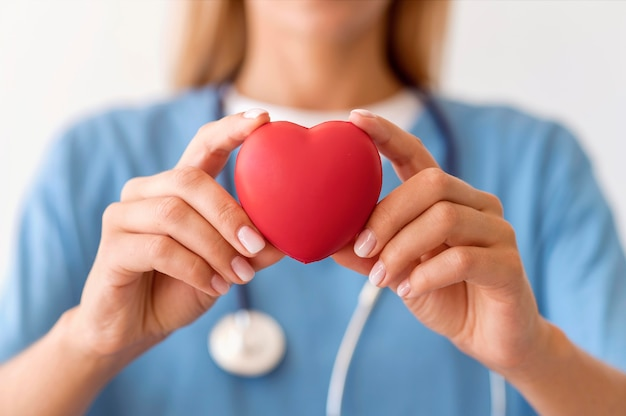 Defocused female doctor holding heart shape