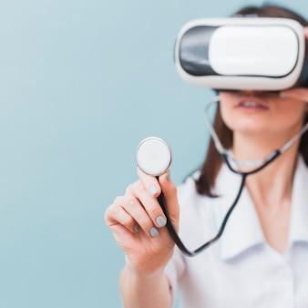 Medico femminile defocused che usando la cuffia avricolare e lo stetoscopio di realtà virtuale