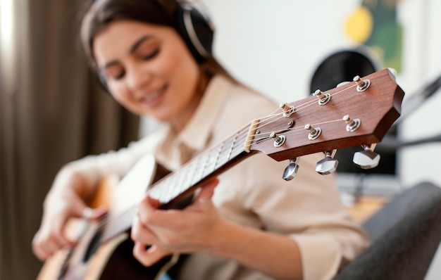Defocused female musician playing acoustic guitar at home