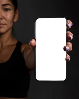 Giocatore di rugby femminile sfocato che tiene smartphone