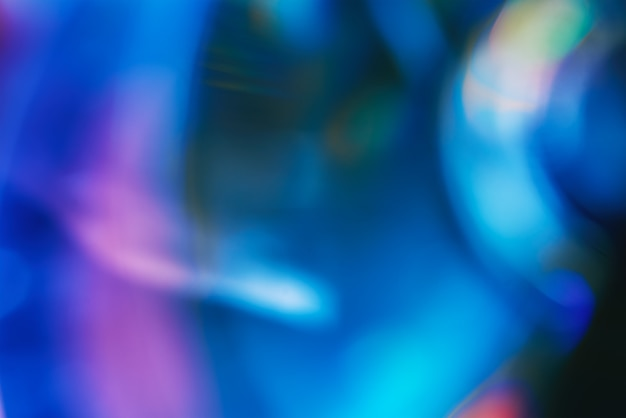 Defocused film texture background with colored lights on dark background. blurred rainbow color light flare for photo effects