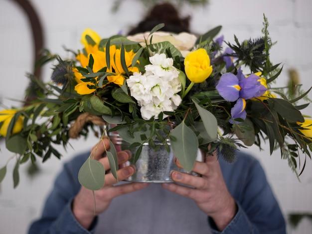 Defocused florist holding flower vase in front of his face