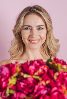 Defocused flower bouquet in front of smiling young woman against pink background