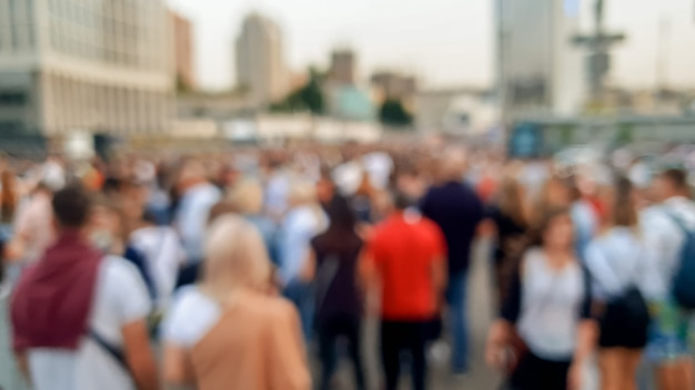 Defocused image of big crowd of people celebrating the carnaval or holidays on the city street