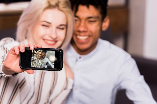 Defocused interracial young couple taking selfie on smartphone