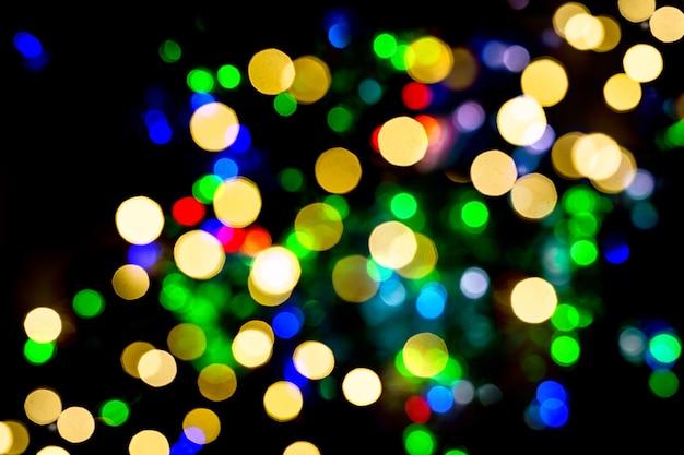 クリスマスの飾りから焦点がぼけたライト。抽象的な光沢のある多色の背景
