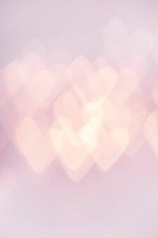 ピンクの背景にデフォーカスライトハート垂直写真