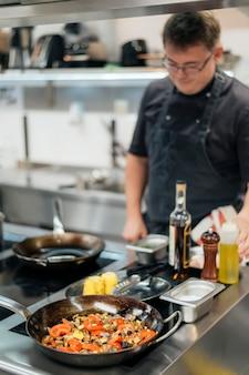 Расфокусированные мужской шеф-повар готовит на кухне