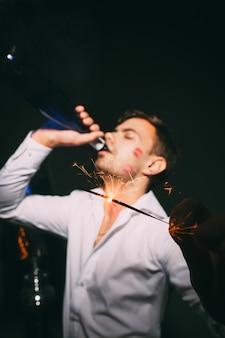 Расфокусированные мужчина пьет из бутылки на фоне партии бенгальский огонь