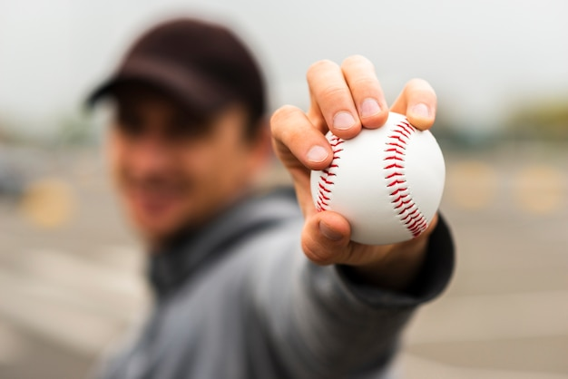 Defocused man holding baseball in hand