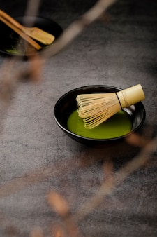 Defocused matcha tea in bowl with bamboo whisk