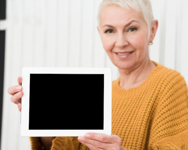 Defocused mature woman holding tablet in hands