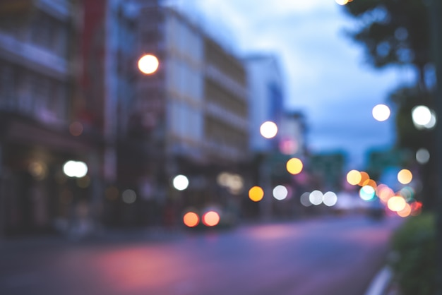 Defocused night city lifewith  cars, people and street lamps, retro style