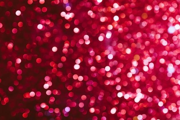 ピンクのきらめくキラキラのボケ味の焦点がぼけますクリスマスと新年のパーティーのお祝いのコンセプト