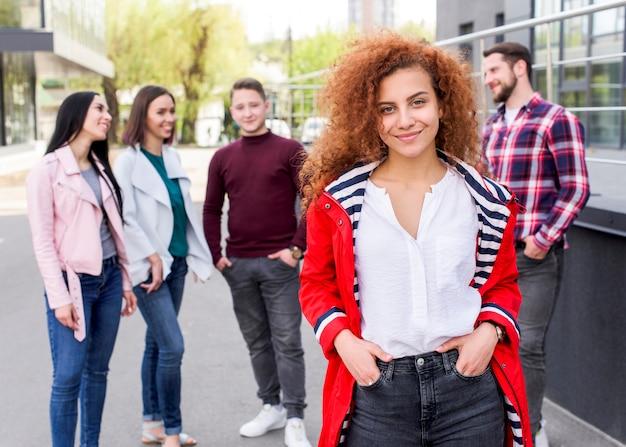 Defocused people standing behind their female friend with curly hairs looking at camera