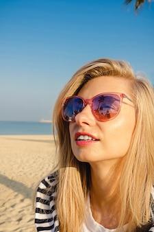 Расфокусированный портрет молодой девушки в белой рубашке с полосами на пляже с солнечными очками, на которых видно, как отражение пальмы счастливо улыбается.