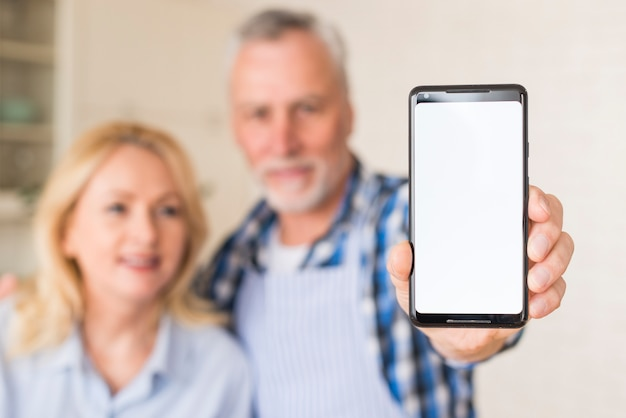 Defocused portrait of a senior couple holding mobile phone with white screen display
