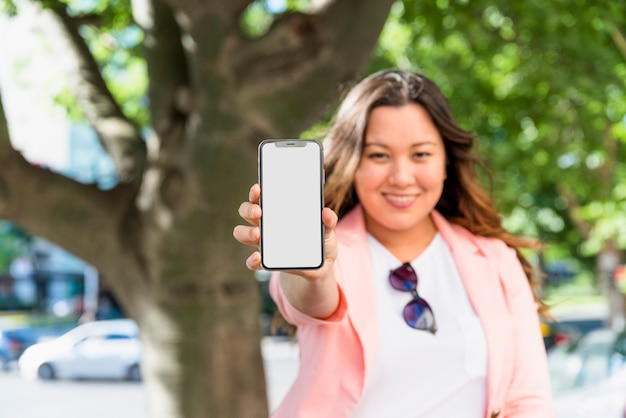Defocused portrait of a young woman showing white display screen of mobile phone