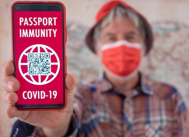 グリーンカードパスポート健康予防接種証明書と携帯電話を保持している焦点がぼけた年配の男性
