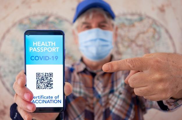 ワクチン接種のグリーンパス健康証明書と携帯電話を保持している焦点がぼけた年配の男性