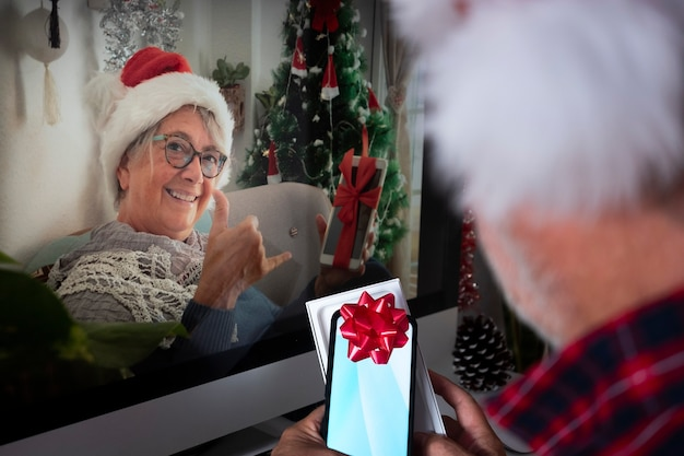 Defocused senior man in video call due to lockdown with the senior wife smiling happy showing the christmas gift. at home with computer and technological devices