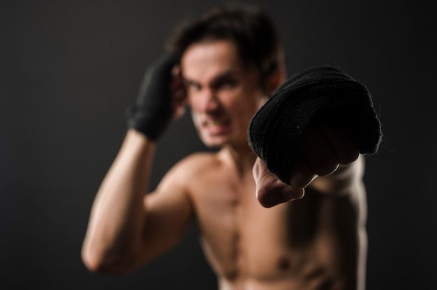 Defocused shirtless muscly man with boxing gloves