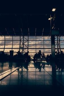 空港を旅行するビジネスマンの焦点がぼけたシルエット。飛行機の搭乗ゲートで待っています。