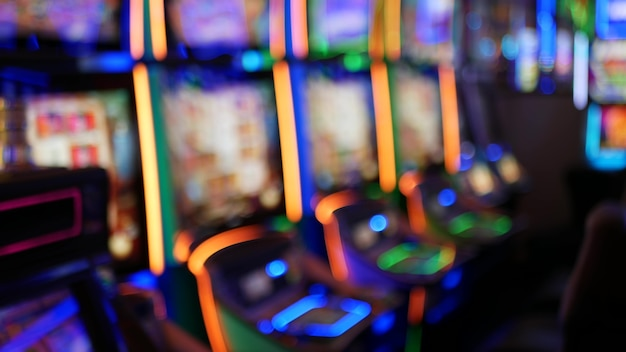Defocused slot machines glow in casino of las vegas, usa. illuminated neon gambling slots.