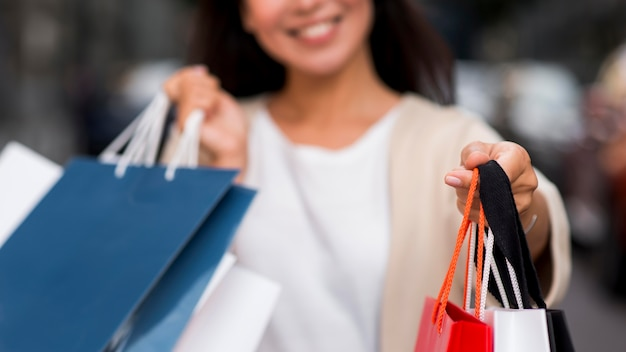 Defocused smiley woman holding shopping bags after sale session