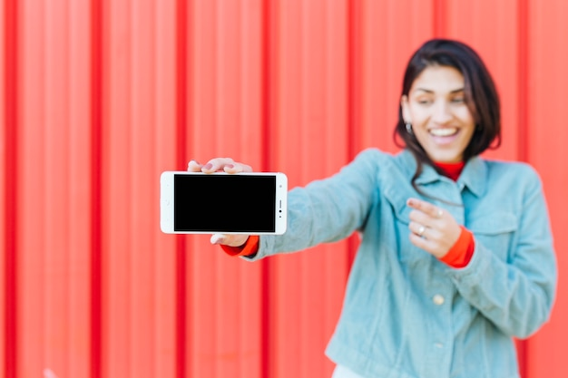 Defocused smiling woman showing cell phone