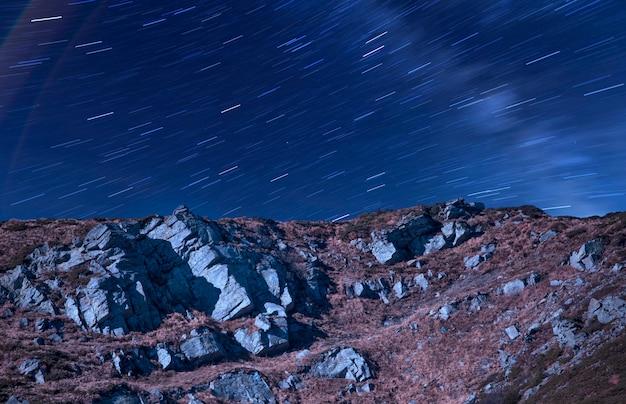 焦点がぼけた星とロッキー山脈の斜面。夜の風景。