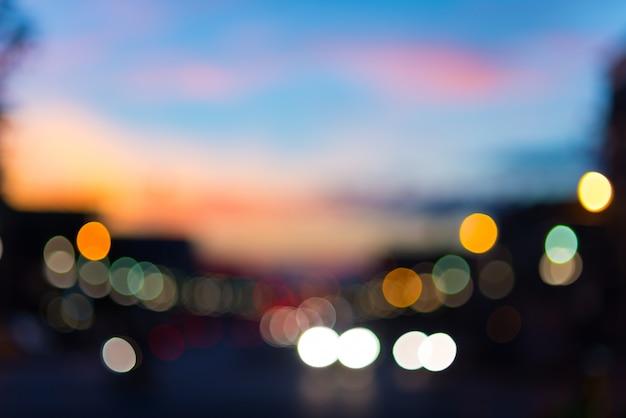 Defocused traffic and city lights on urban big street at dusk.