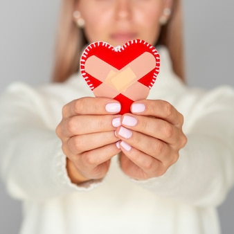 Defocused woman holding fixed heart